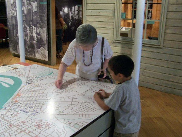 Two generations exploring the Muscatine city map at the Pearl Button Museum